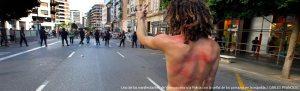 Espalda de un huelguista que desafía a lo antimotines en Valencia Foto: El País