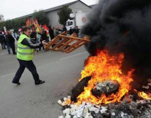 Un manifestante arroja un palé a una barricada en llamas EFE