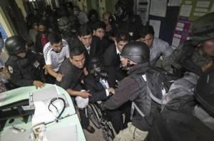 En silla de ruedas y con máscara antigás el presidente de Ecuador, Rafael Correa, es sacado por el ejército del Hospital de la Policía donde fue secuestrado el 30 de septiembre, día de la sublevación de uniformados