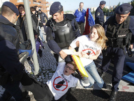 Activistas anti-OTAN son llevados por agentes de la policía REUTERS