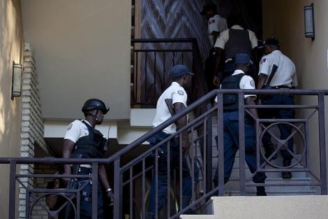 Varios policías suben por unas escaleras del Hotel en que se aloja Duvalier Puerto Príncipe