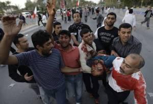 Opositores trasladan a un herido al hospital, tras el ataque perpetrado este viernes por el ejército de Bahrein. Foto: AP