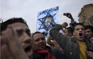 Manifestantes egipcios con un retrato de Mubarak dentro de la estrella de David, símbolo de Israel(AP Photo/Emilio Morenatti)