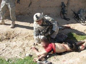 """Capitán del ejército norteamericano Jeremy Morlock posa sonriente mientras sostiene por el pelo la cabeza de un campesino afagano asesinado por el """"Kill Team"""""""