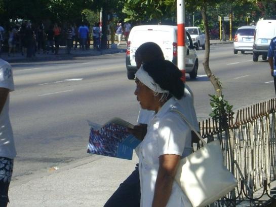 Cubanos leen folletos con Lineamientos para el desarrollo económico y social del Partido y la Revolución en la Habana, Cuba