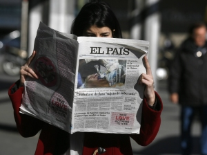 "A woman poses with a first edition copy of Spanish newspaper El Pais in central Madrid...A woman poses with a copy of the January 24 first edition of Spanish newspaper El Pais in central Madrid January 24, 2013. Spain's influential El Pais newspaper withdrew what it said was ""false photo of Hugo Chavez"" that it had published in its on-line and print editions on Thursday. The grainy photo that El Pais originally splashed on its front page, billed as a global exclusive, portrayed the head of a man lying down with a breathing tube in his mouth. REUTERS/Andrea Comas  (SPAIN - Tags: MEDIA POLITICS)"