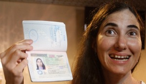Cuba's best-known dissident, blogger Yoani Sanchez poses with her passport after arriving at Guararapes International airport in Recife