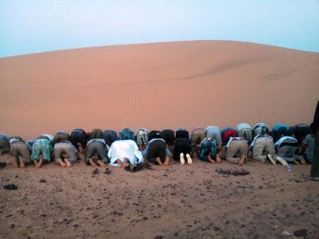 Saharauis rezando hacia La Meca al caer la tarde