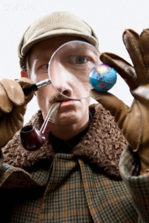 A Man Dressed up As Sherlock Holmes Looking at a Tiny Globe Through a Magnifying Glass