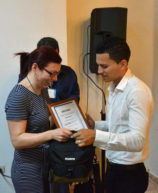Miriam Nather de Cuba Sí entrega 1er Premio del concurso El rasguño en la piedra a José Carlos Roque Vila.